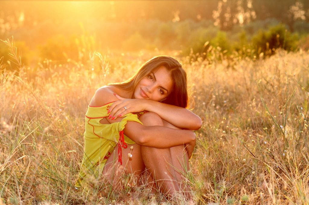 Seated lady in grass under morning sun rays