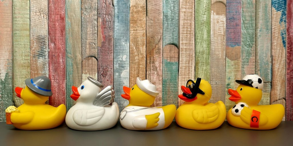 5 rubber ducks in a row with wooden backdrop