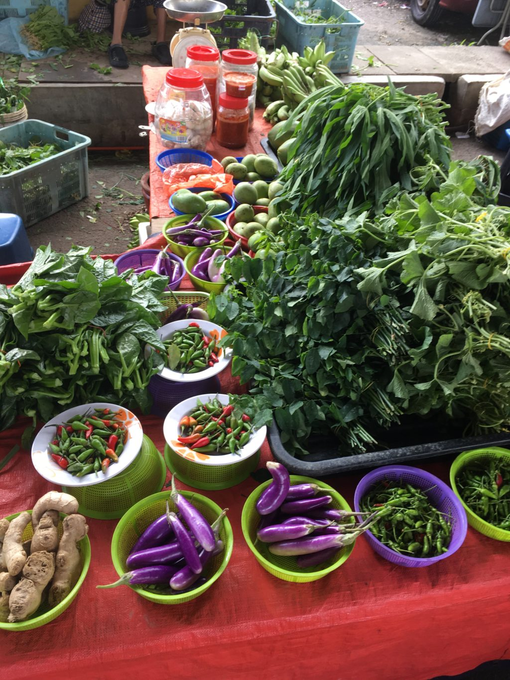 Vegetables stall at Pasar Borneo with basket of brinjals, midin and paku-pakis