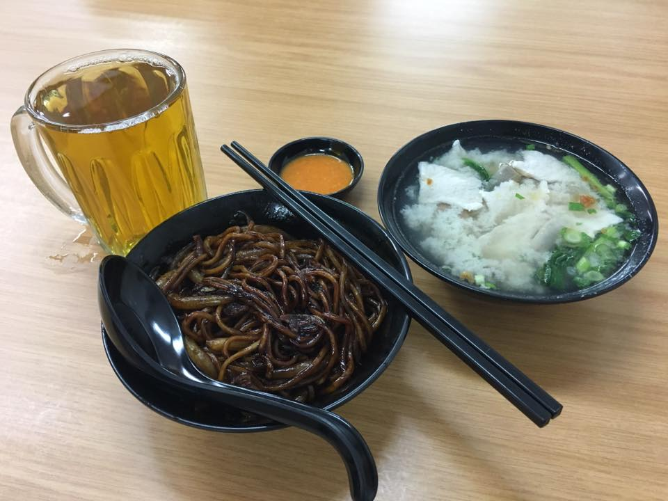 Bowl of dried pork noodle in black sauce with soup and chinese tea on side