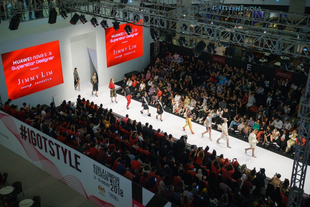 Aerial of fashion runway with models doing catwalk at centre surrounded by audience