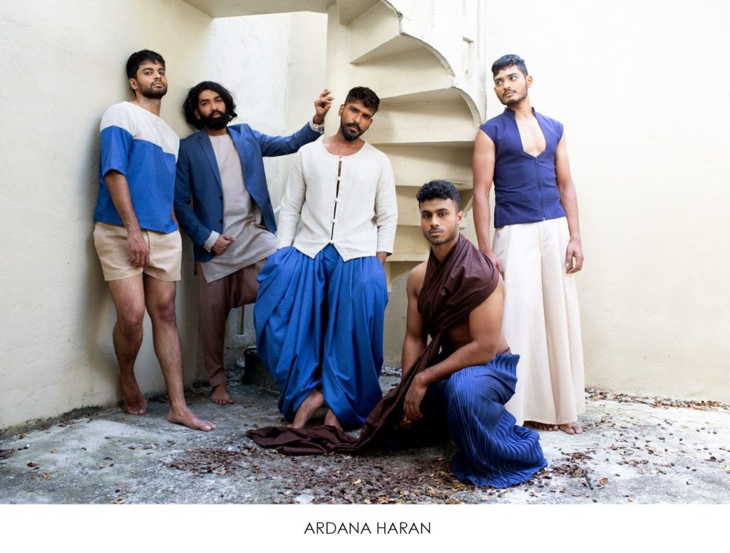 5 male models in designer's Indian inspired wear standing against stairwell