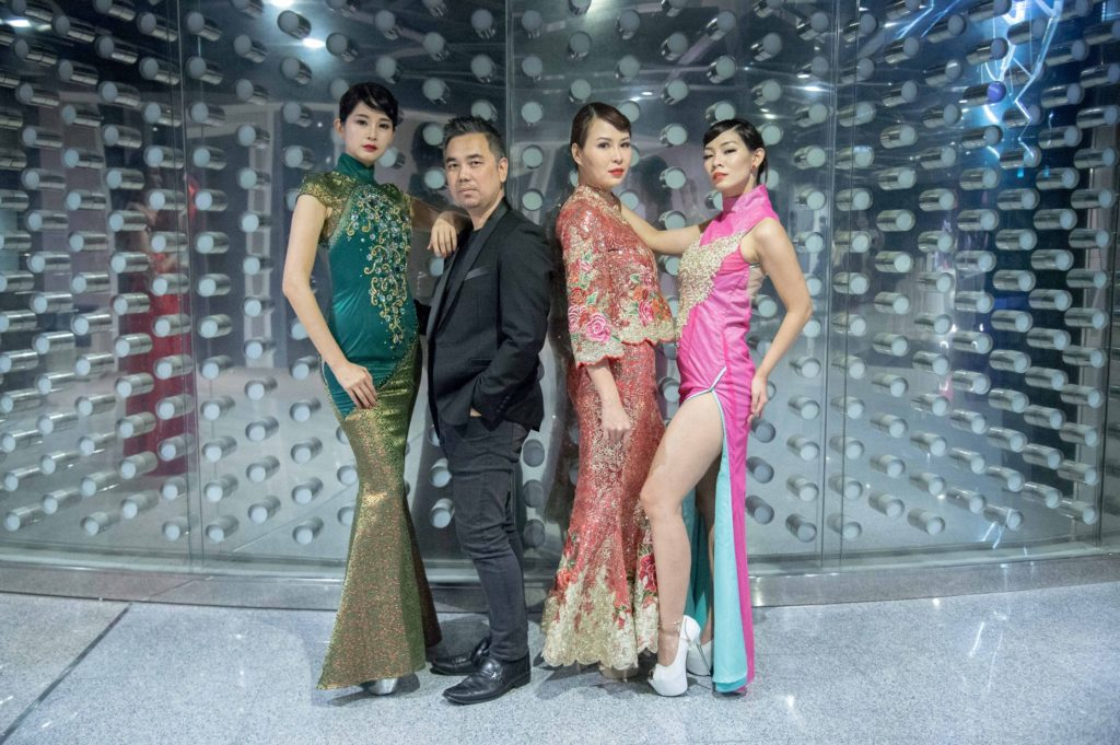 3 models parading Chinese inspired wear next to designer