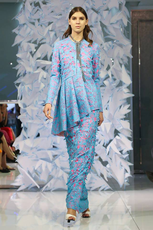 Model in blue outfit by designer on runway