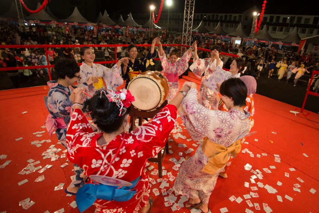 Dancers in kimono holding hands and performing on red stage