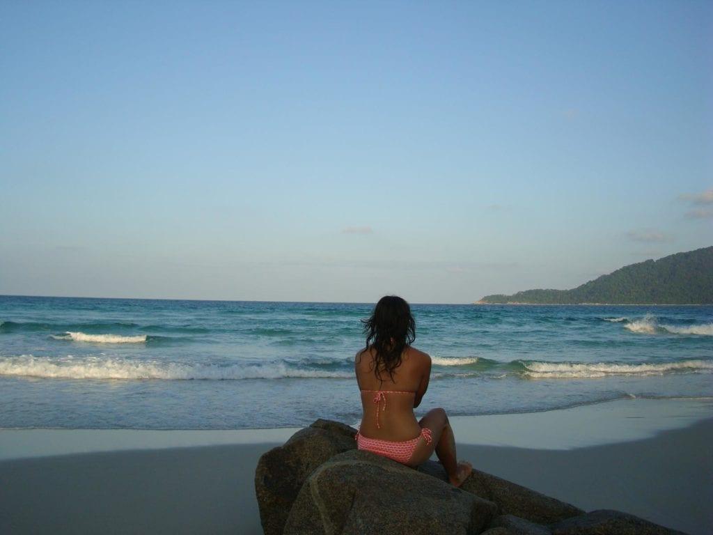 Bikini lady seated on rock by the beach