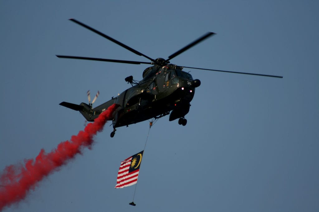 Helicopter in aerial display with flag below