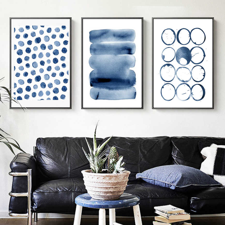 3 blue themed wall art hangings above sofa