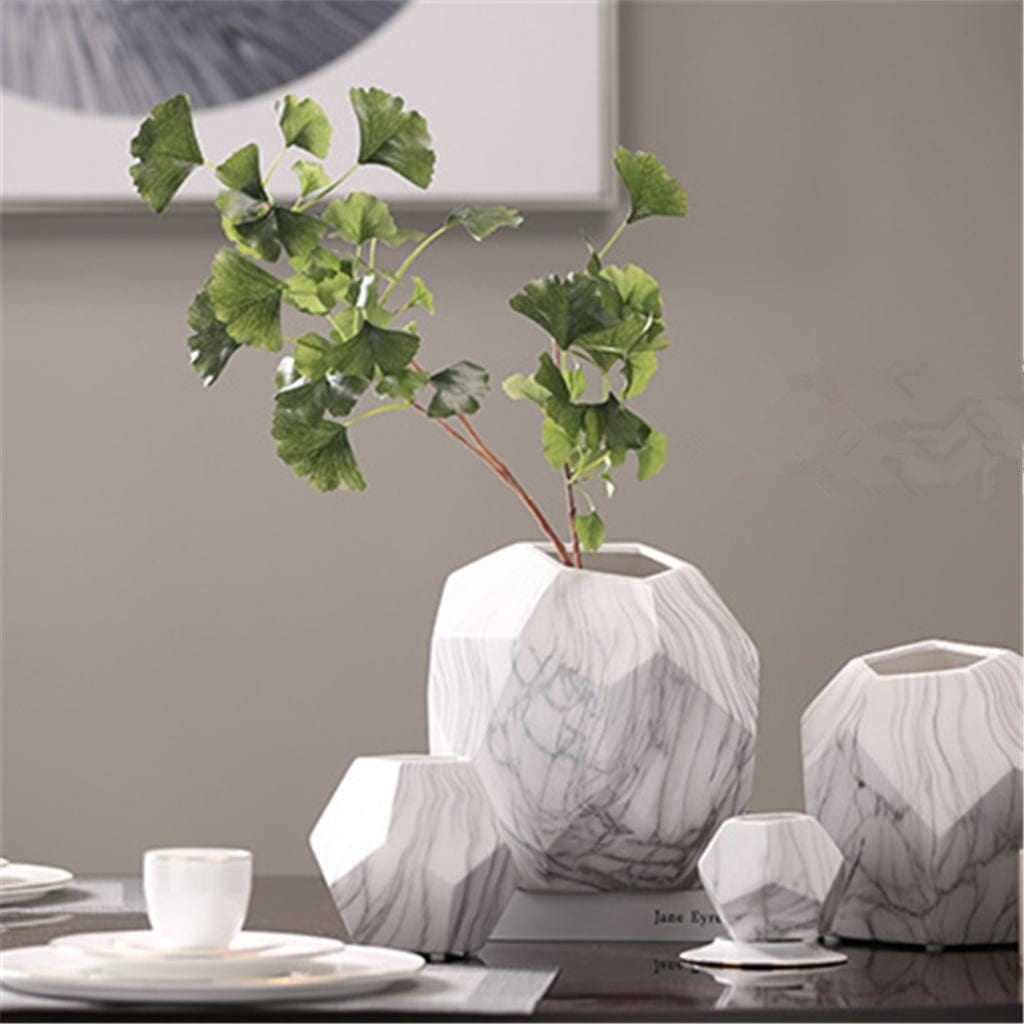 A set of geometric ceramic marbling flower vases on table with green leaves in one vase
