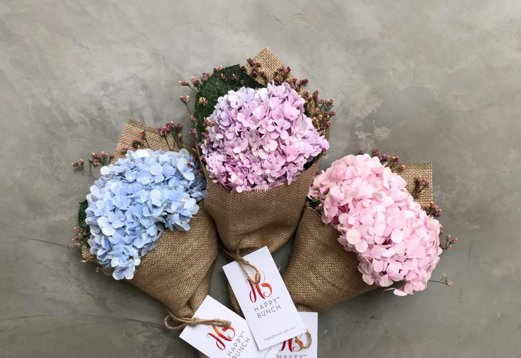 3 floral bouquets in brown wrapped paper