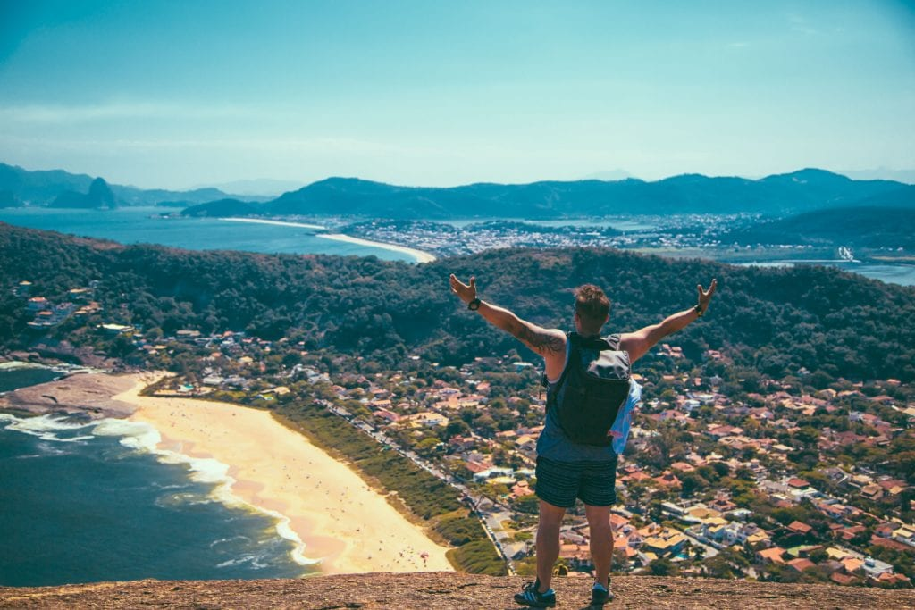 Traveller with hands outstretched facing view of ocean and beach