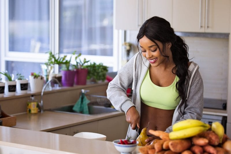 woman cutting vegetables for a healthy lunch after exercising