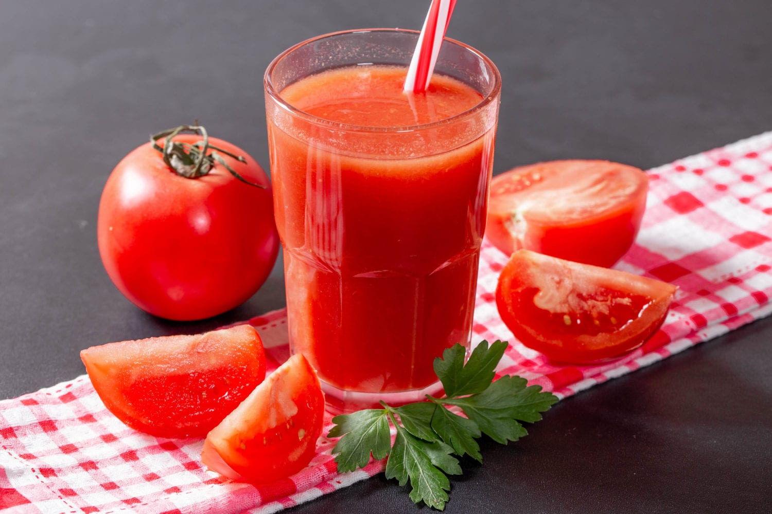 Tomato juice with sliced tomatoes on table