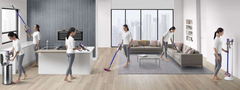 woman using dyson vacuum cleaner around the house