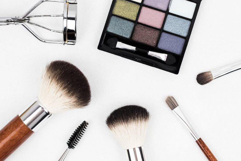 set of makeup and brushes across a white table