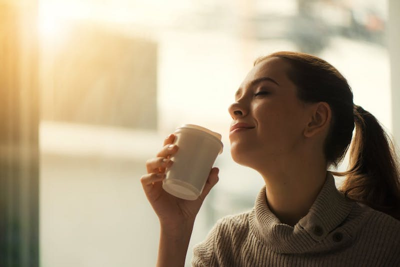Woman having coffee in a sunny morning