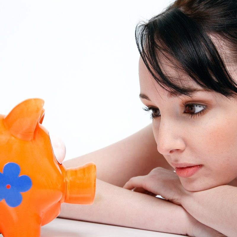 Girl staring at piggy bank hoping to save more money