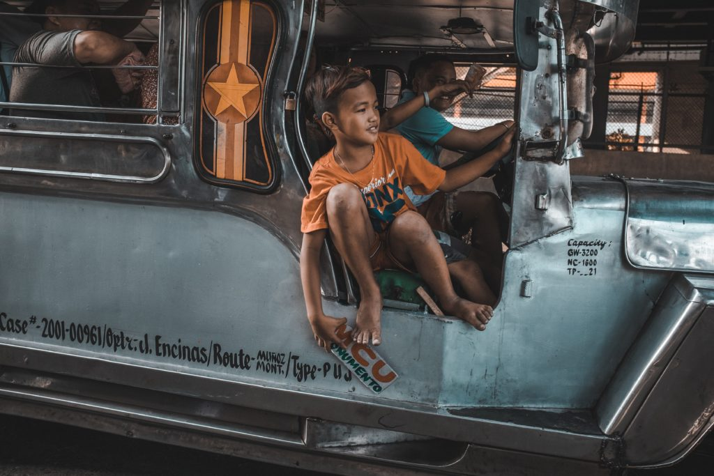 Boy taking a jeepney in Manila during a hot day