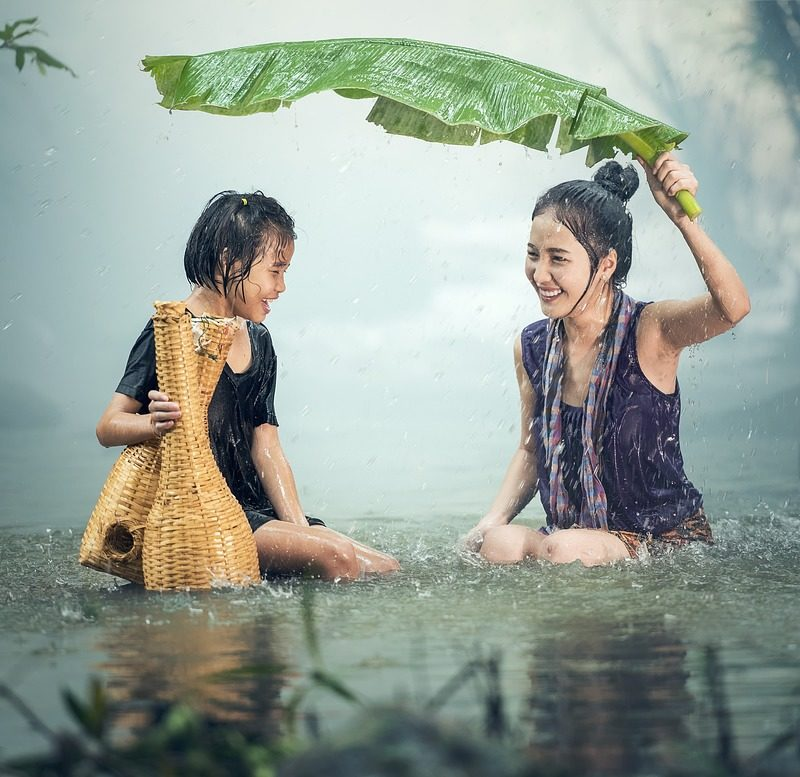 Mother having fun with child on the rain