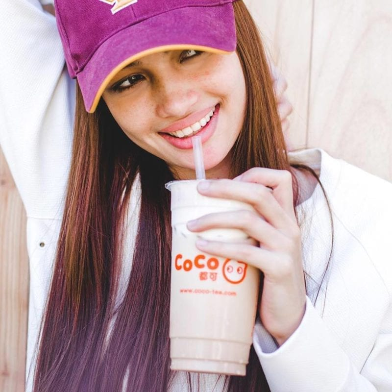 lady in pink cap sipping Coco bubble tea