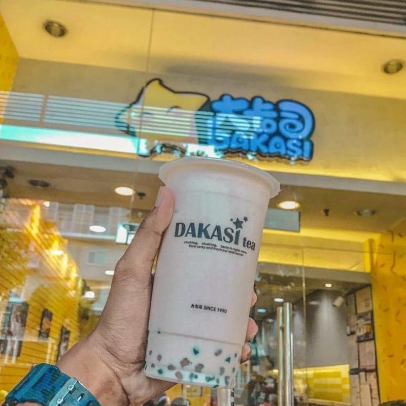 Dakasi shop facade with hand holding bubble tea