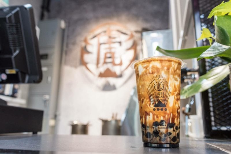 Cup of Tiger Sugar bubble tea on counter with logo at back