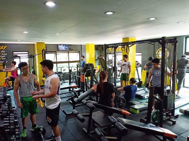 members in open gym area chatting and training