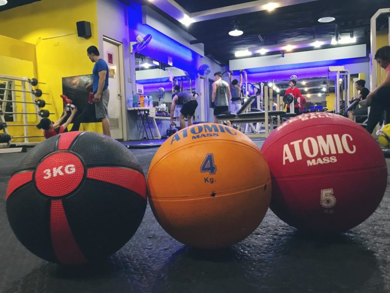 3 weight balls in front on floor of gym