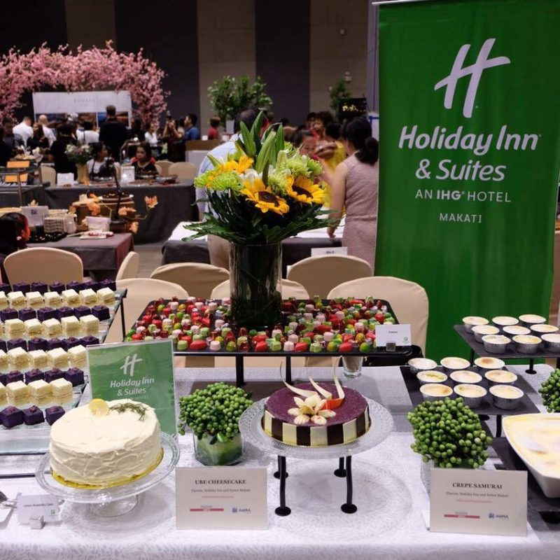 Array of desserts on table with diners in background
