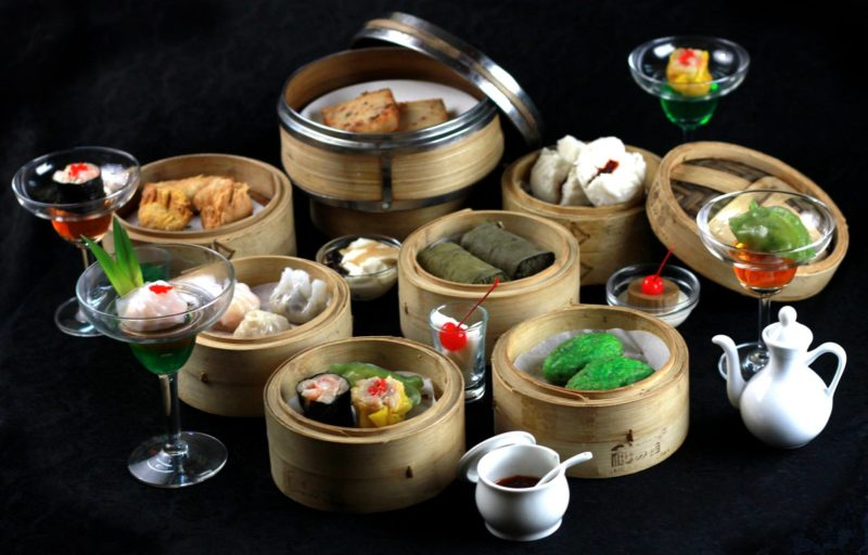 Trays of dim sum in all varieties placed on black backdrop