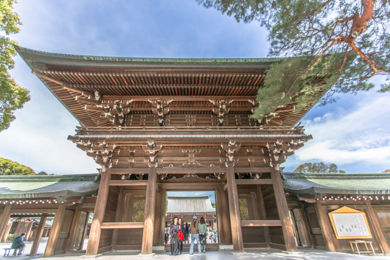 High gates at Meiji Shrine with people entering below archway