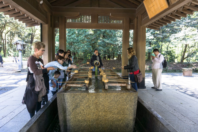 Cleansing station with people scooping water to clean hands