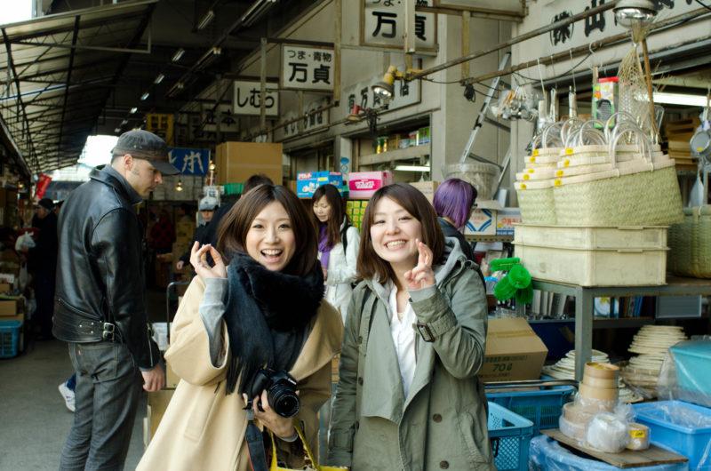 2 ladies standing in front of Tsukiji market stalls