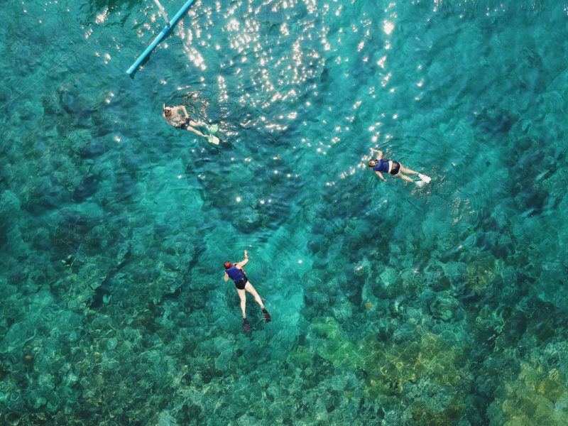 Aerial view of 3 divers swimming on surface of sea