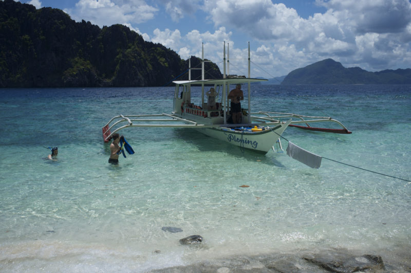 Clear waters on Palawan with boat and diver coming in to beach