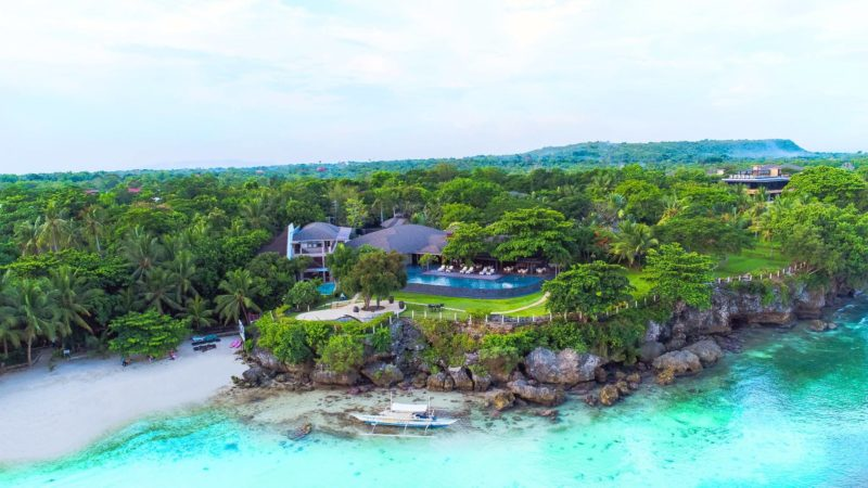 Faraway view of Amorita Resort with green landscapes and blue waters