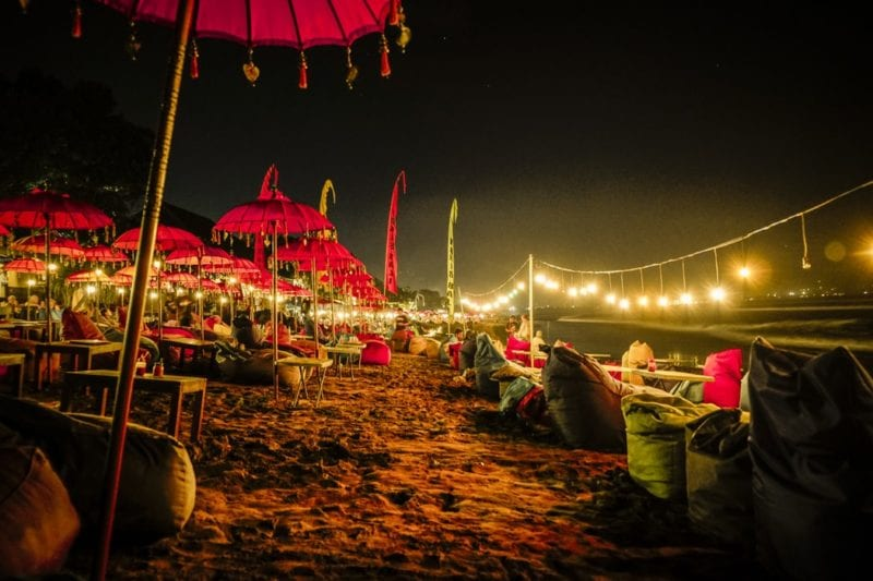night time by the beach with neon lights and parasols
