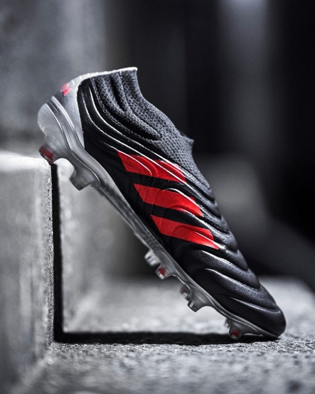 Adidas COPA in black with red stripes propped on stairs