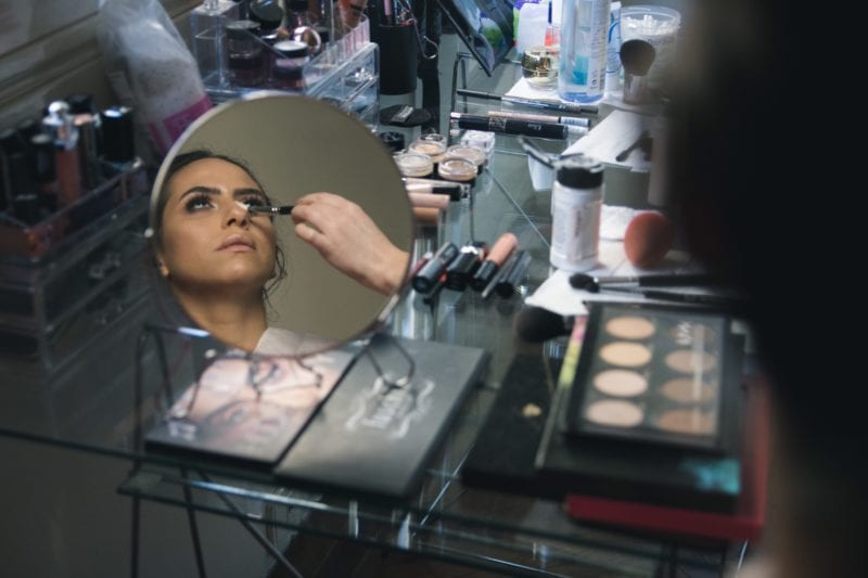Reflection of lady in mirror and make up being applied with palettes all around