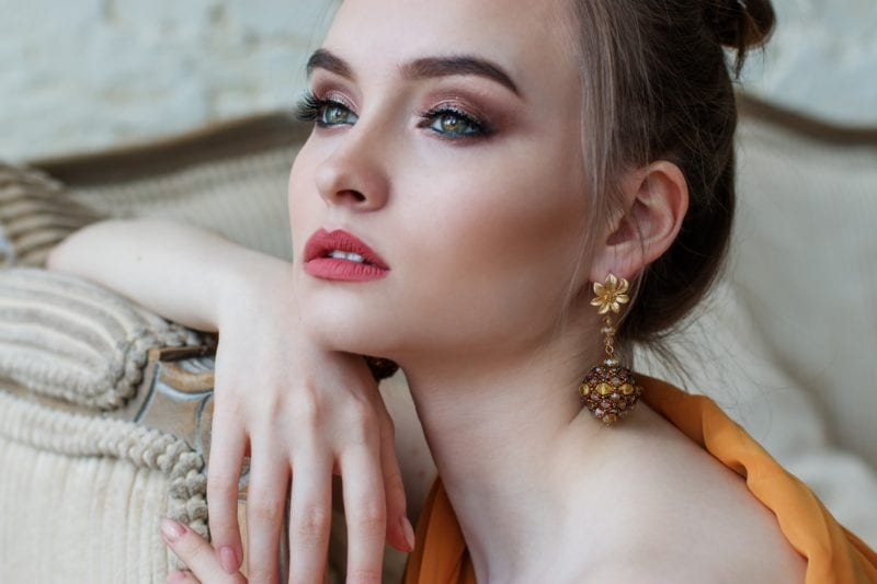 Lady with make up in full leaning on hand and has gold earrings on