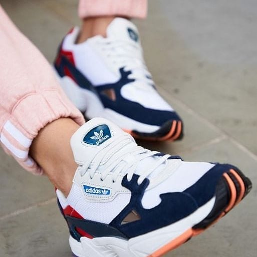 woman wearing blue and white sneakers with orange stripes and pinks joggers