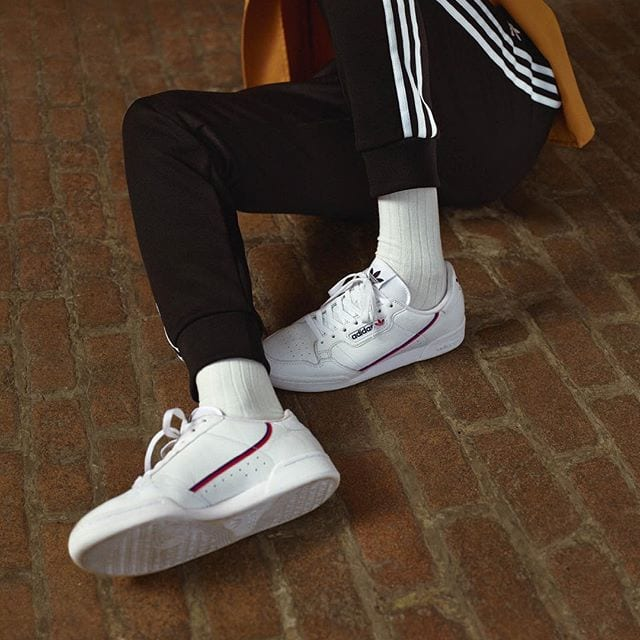 man in black pants wearing a pair of white leather sneakers with blue and red stripes