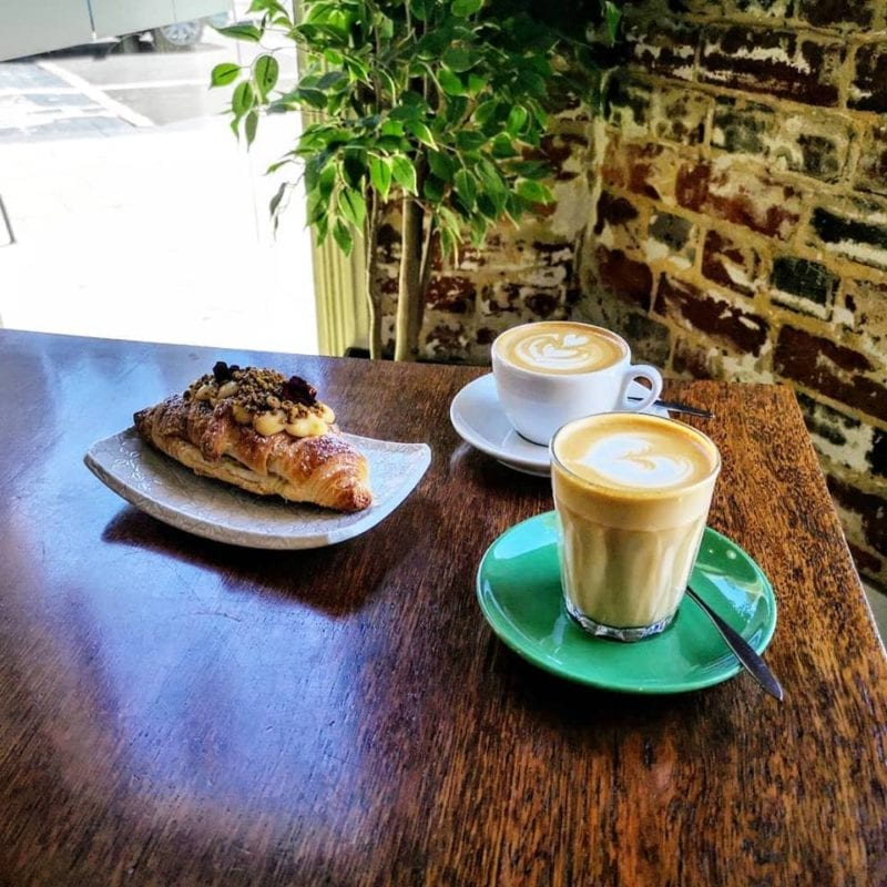 2 cups of coffee and pastry on wooden table