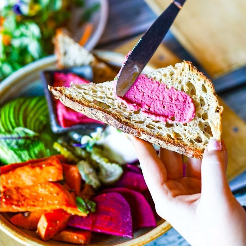 Pot of Gold -dish with purple beet root spread on toast using knife above plate of treats