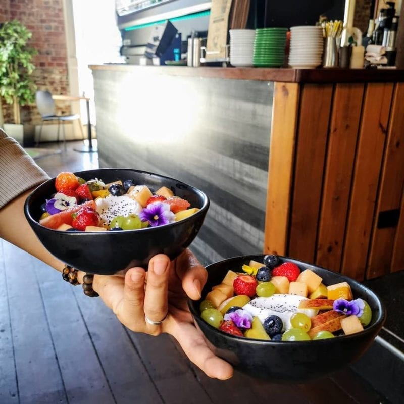 2 bowls of muesli with fruits held in one hand