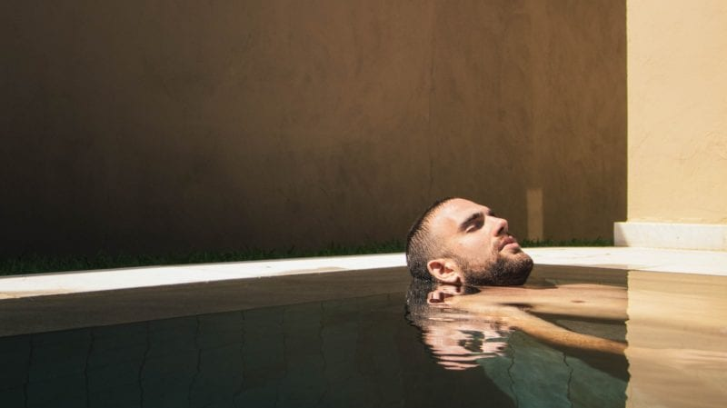 man lying in a water spa and relaxing