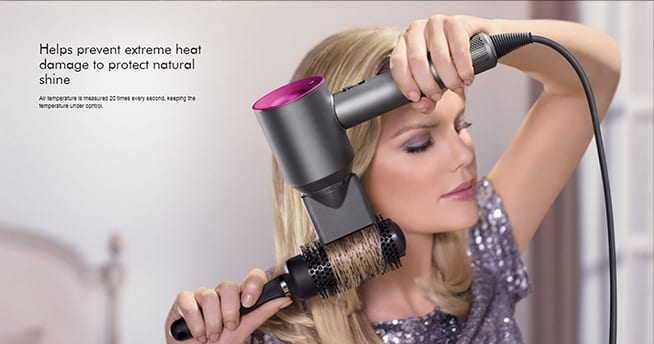 caucasianwoman blowdrying and styling her hair with a Dyson Supersonic Hair dryer in Iron and Fuchsia color