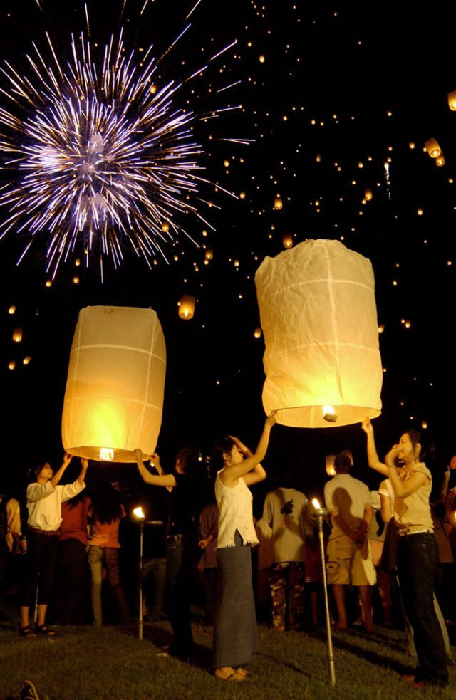 People floating lanterns with fireworks backdrop