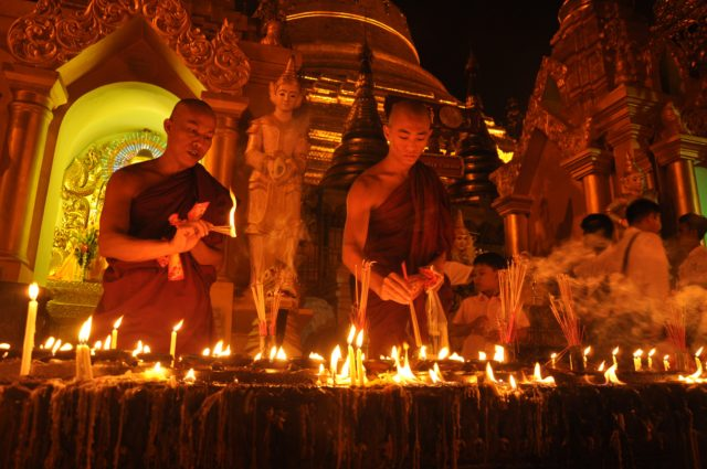 Monks lighting candles