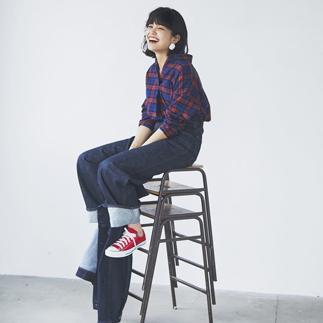 model wearing flannel shirt and jeans with red sneakers